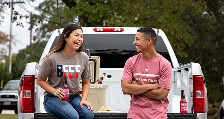 People wearing Beef merch sitting on truck bed