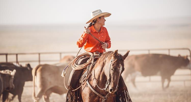 Image of woman on horse with lasso.